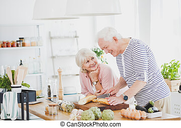 Happy old man cuts the baguette