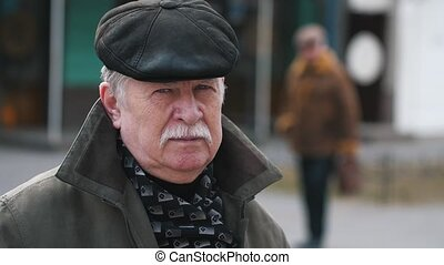 Happy old man with a mustache in a cap standing in a street...