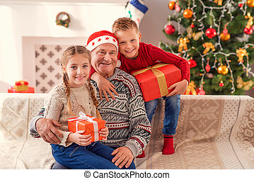 Happy old man with his grandchildren on Christmas - Friendly...