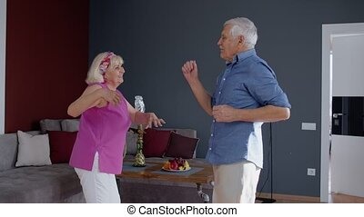 Happy old senior couple dancing having fun celebrating retirement anniversary in living room at home
