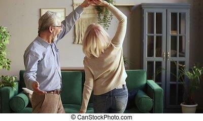 Happy old senior romantic couple dancing in modern living room