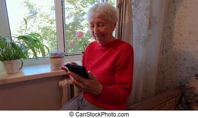 Happy old senior woman holding smart phone, looking at cellphone screen using social media at home, older people and technology concept
