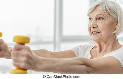 Happy old woman lifting dumbbells