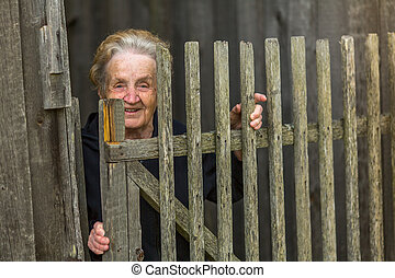 old woman stands behind a wooden