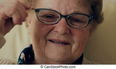 Happy old woman with eyeglasses smiling and looking at camera.