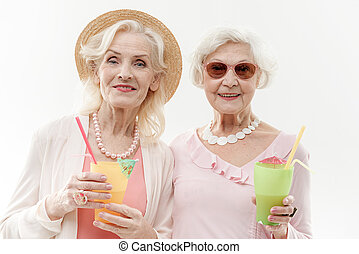 Happy old women having fun with exotic drink