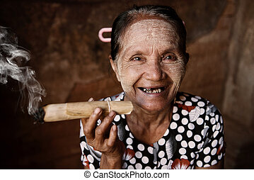 Happy old wrinkled Asian woman smoking traditional tobacco....