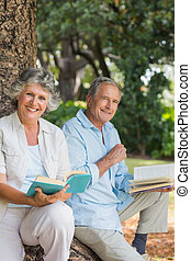 Happy older couple reading books together sitting on tree trunk looking at camera in the park on sunny day