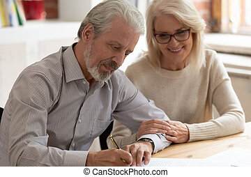 Happy older family couple husband and wife sign legal paper