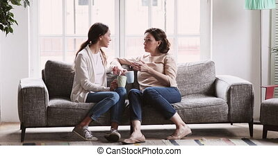 Happy older mother and adult daughter chatting in living room