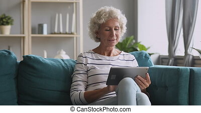 Pleasant smiling elderly mature woman resting on sofa, using digital tablet alone at home. Happy older pensioner web surfing information, chatting on social networks, studying or shopping online.