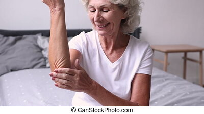 Happy older senior retired woman moisturizing elbow with ...
