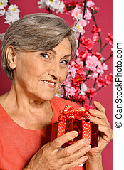 Happy olderly woman holding gift