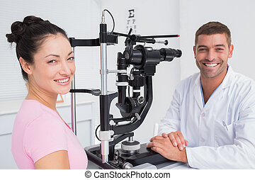 Happy optician and female patient with slit lamp