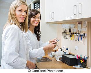 Happy Opticians Repairing Glasses In Workshop - Portrait of ...