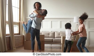 Happy overjoyed african family celebrate moving day relocation together, black parents embrace and cute little children jump laugh in living room with boxes, new house purchase, mortgage investment