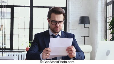 Happy overjoyed businessman opening envelope reading great news in letter