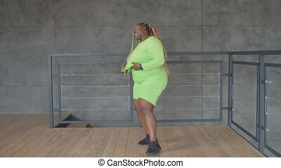 Happy overweight african female dancing at home - Happy ...