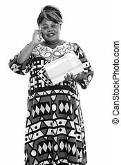Happy overweight African woman talking on the phone and holding gift box