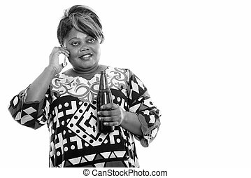 Happy overweight African woman talking on the phone while holding beer