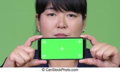 Happy overweight Asian businesswoman showing phone - Studio...