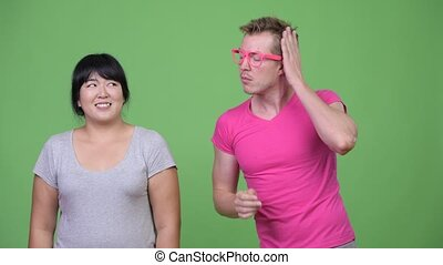 Happy overweight Asian woman and young gay man smiling...