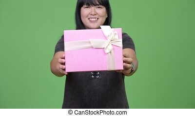 Happy overweight Asian woman giving gift box - Studio shot...