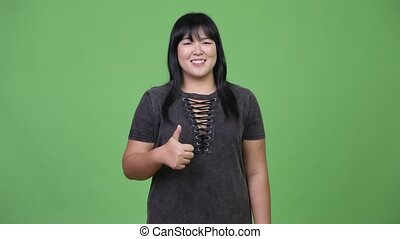 Happy overweight Asian woman giving thumbs up - Studio shot...