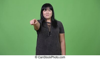 Happy overweight Asian woman pointing at camera - Studio...