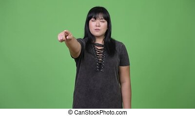 Happy overweight Asian woman pointing finger - Studio shot...