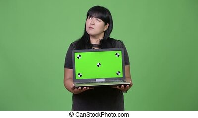 Happy overweight Asian woman thinking while showing laptop -...