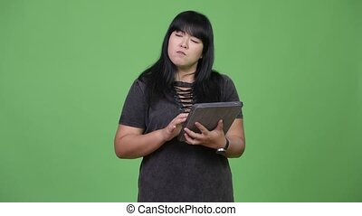 Happy overweight Asian woman thinking while using digital...