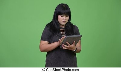 Happy overweight Asian woman using digital tablet