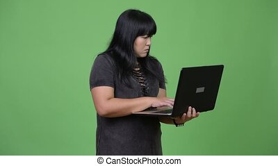 Happy overweight Asian woman using laptop - Studio shot of...