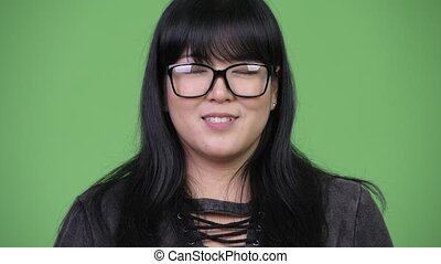 Happy overweight Asian woman with eyeglasses - Studio shot...