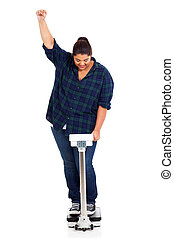 happy overweight woman lost weight on scale