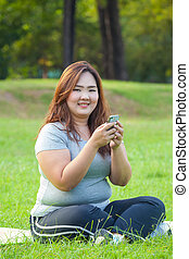 Happy overweight woman using mobile phone