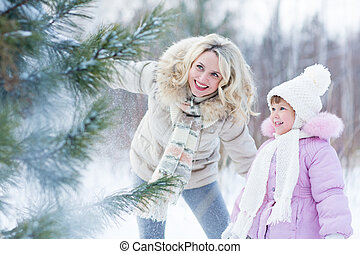 Happy parent and child playing with snow in winter outdoor