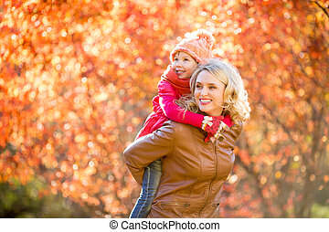 Happy parent and kid family walking together outdoor in fall par