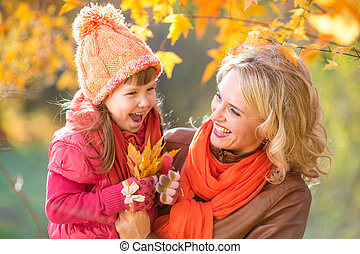 Happy parent and kid holding autumn yellow leaves outdoor.