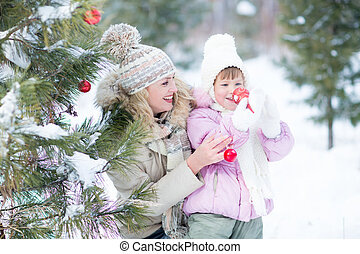 Happy parent and kid playing with christmas tree decorations outdoor