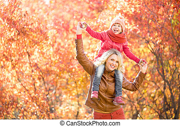 Happy parent and kid walking together outdoor in autumn park. Yellow and red tree leaves. Child sitting on her mother's neck.