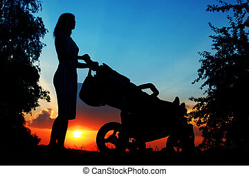 happy parent silhouette on the nature of the sunset with a sidecar