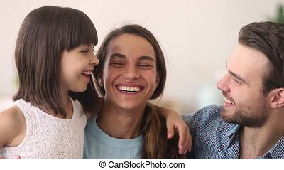 Happy parents and child daughter embracing laughing looking...