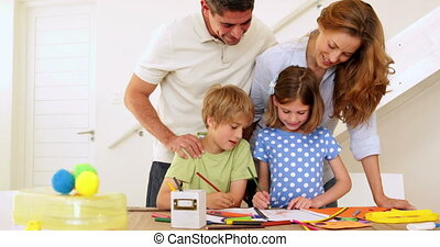 Happy parents and children drawing together at the table...