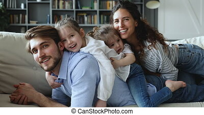 Happy parents and cute daughters cuddling at home on sofa