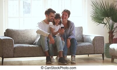 Happy parents and daughter laugh look at phone at home