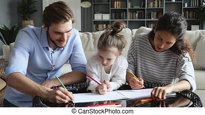 Happy parents and kid daughter enjoying drawing together at home