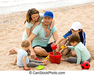 Happy parents and kids playing with sand