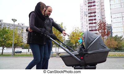 Happy parents are going with a baby carriage in autumn